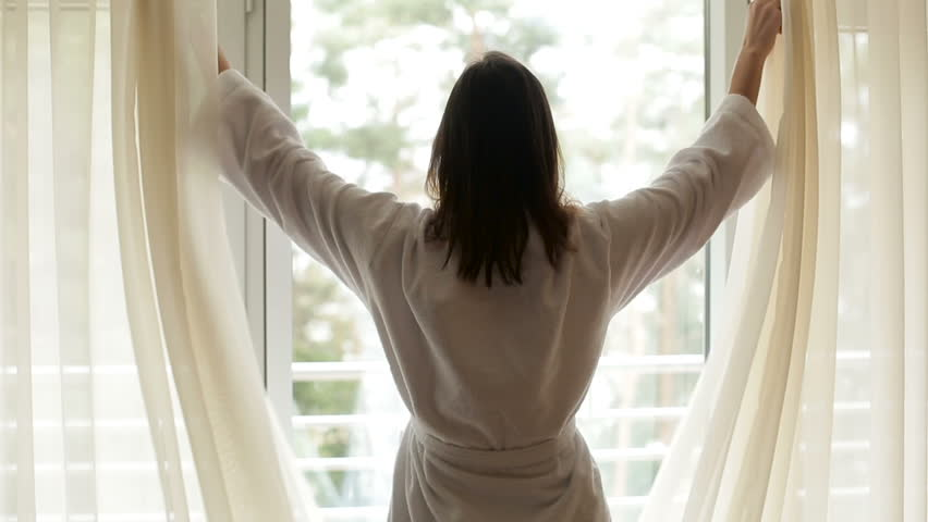 girl in a white robe comes out from the left side to the window and opens the curtains #22531900