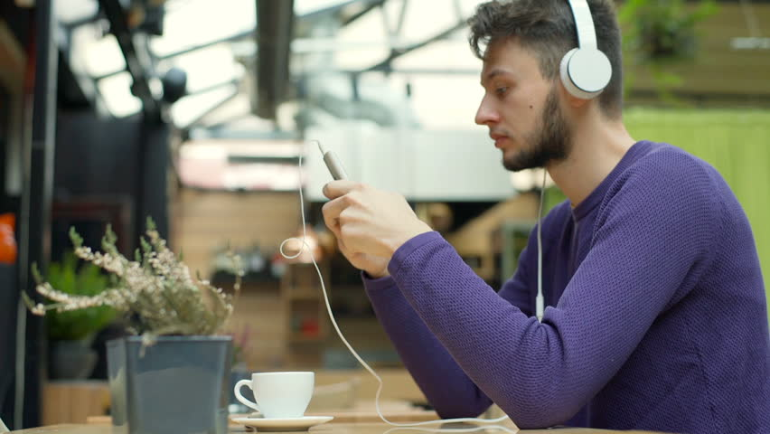Boy smiling to the camera while listening music and texting on smartphone, steadycam shot  | Shutterstock HD Video #22561573
