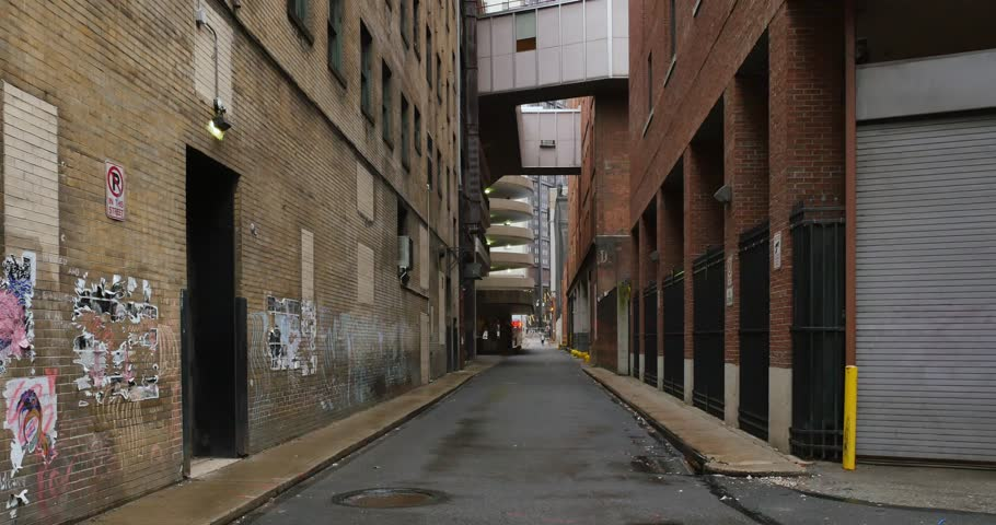 A daytime overcast establishing shot of an empty alley in a big city.  Use as an abandoned, shelter-in-place, quarantine, social distancing concept. Perhaps during a pandemic COVID-19/Coronavirus.