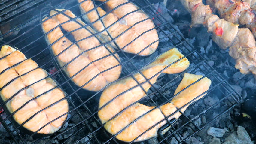 Salmon fish grilled at bbw or barbecue. Healthy food, meal of steak fillet roasted, cooking on fire. Delicious seafood gourmet closeup, fresh lunch, cuisine. Slices of sea meat filet fried at picnic.