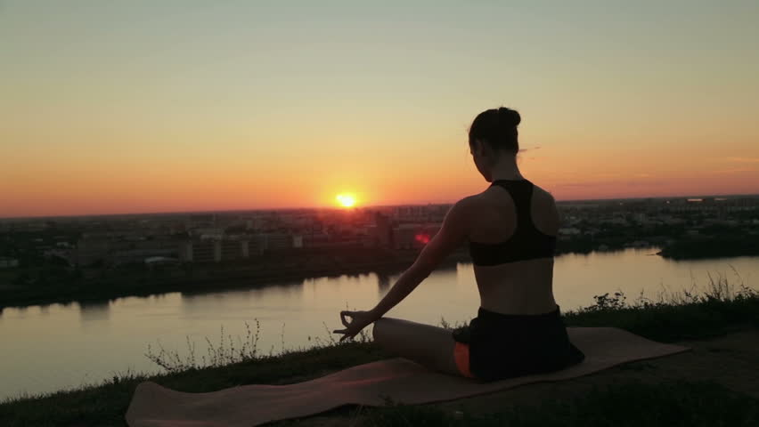 6 shots. Sporty woman in lotus position in the park at sunset. Lotus mudra. Sunset light, golden hour, lens flares. Freedom, health and yoga concept   Shutterstock HD Video #22585825