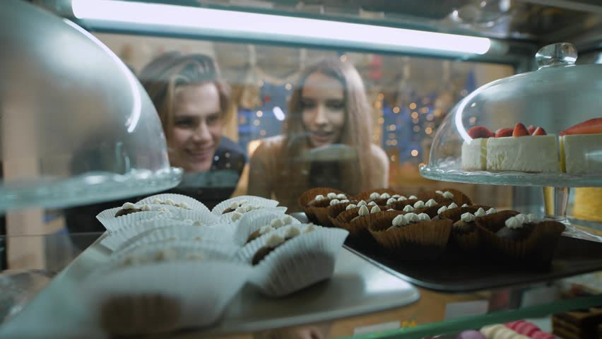 Beautiful couple of young people in a candy store. The girl and the guy chosen Cake and desserts for themselves. Showcase pleasantly decorated