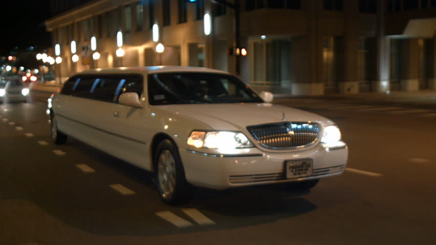 stretched limo driving urban city streets night #22593112