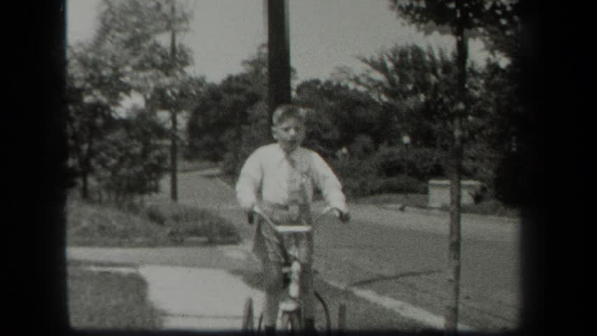 NEW YORK 1939: a boy and his bicycle on the sidewalk at daytime #22597885