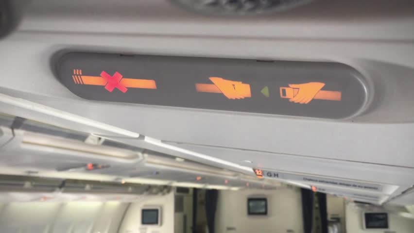 No Smoking and Fasten Seat Belt Sign in an Airplane. Close-Up. Zoom In.