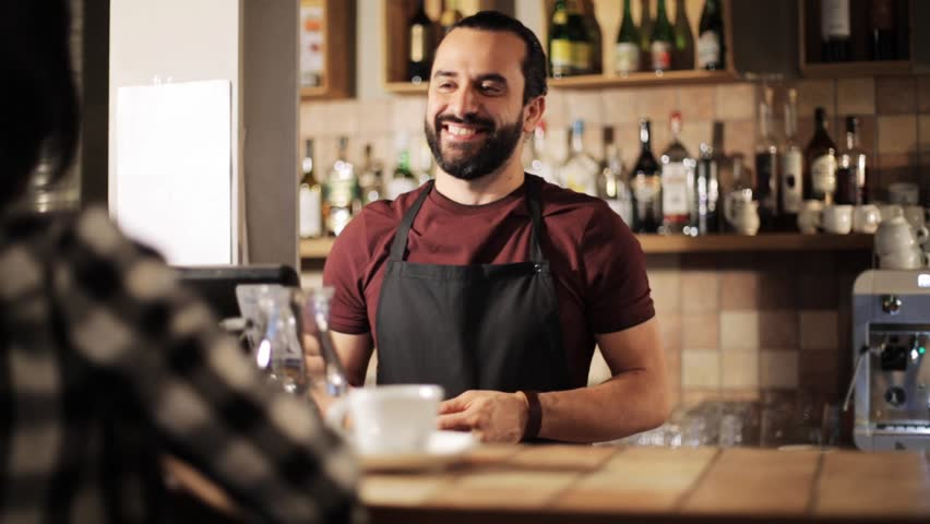 small business, people and service concept - happy man or waiter with cup serving customer and taking money payment at coffee shop