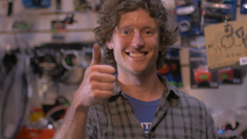 A handsome millennial small business owner smiles and gives a thumbs up in his retail bike shop
