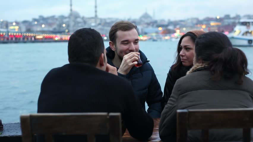 Group of Turkish friends drinking cay, traditional tea in Turkey. They are two boys and two girls sitting by the river in Istanbul. Friendship and lifestyle concepts.   Shutterstock HD Video #22720414