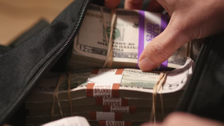 Closeup of a sports bag being open full of money.