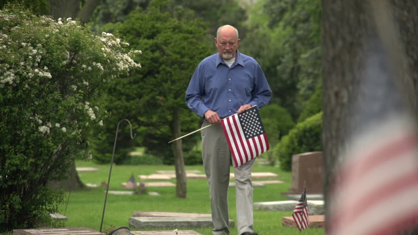 Older man walking through cemetery holding US flag