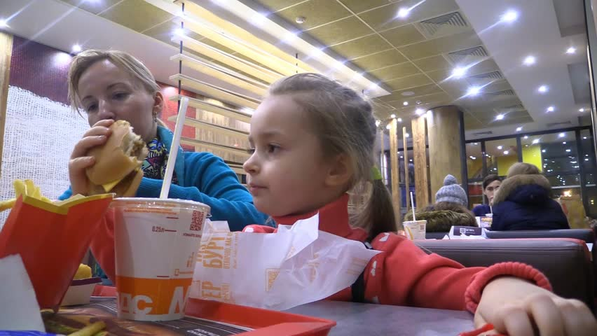 Little girl and mom eating hamburger, fries potato and drink cola in eatery fastfood McDonald's. Moscow - 2017.