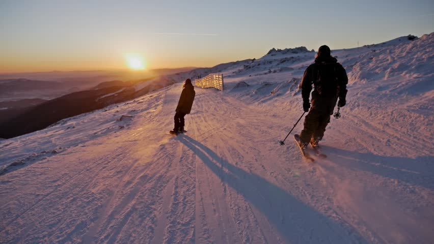 Slowmotion footage of a skier and snowboarder riding the slope during a beautiful sunset. | Shutterstock HD Video #22754083