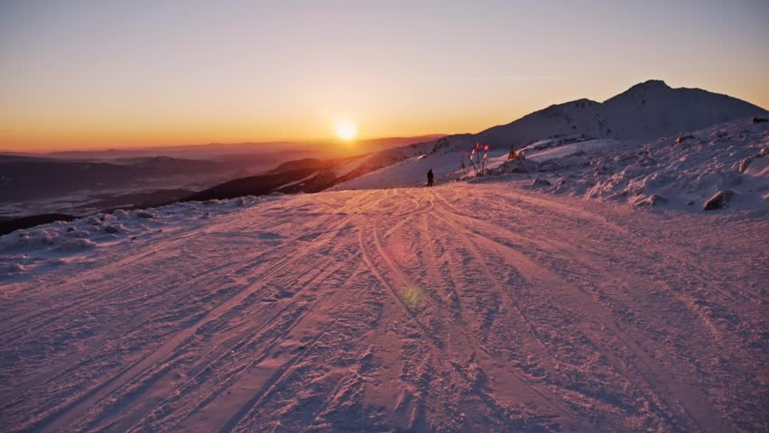 Slowmotion footage of a skier and snowboarder riding the slope during a beautiful sunset. | Shutterstock HD Video #22754128
