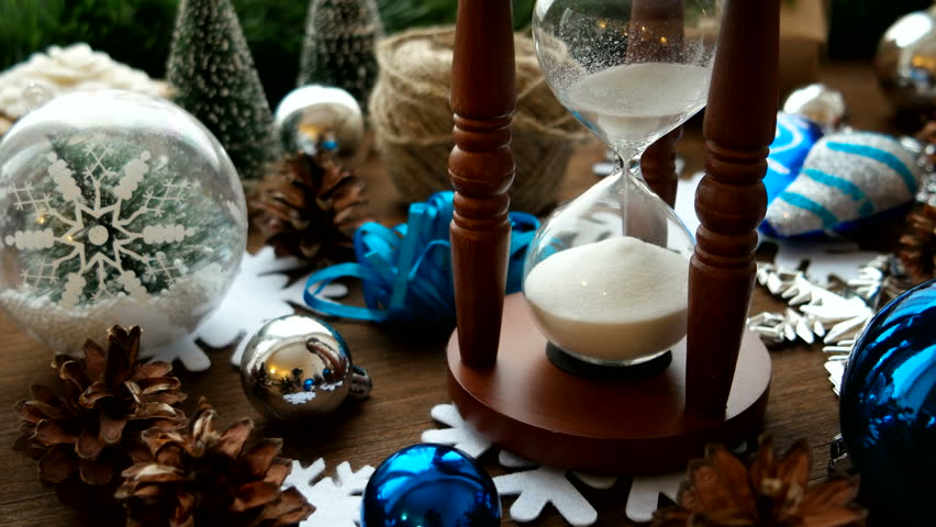 Christmas and New year background with presents, ribbons, balls and different green decorations on wooden background. Wooden hourglass measures time till holiday. | Shutterstock HD Video #22767241