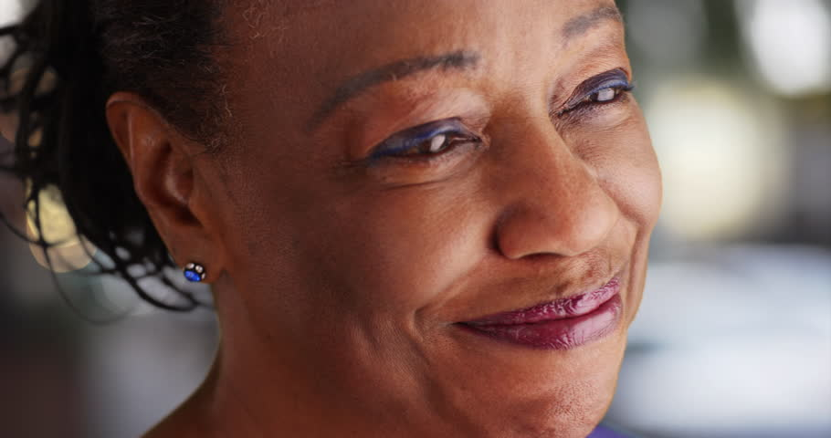 A close-up of an elderly black woman looking into the distance. A tight shot of an older African American woman. 4k