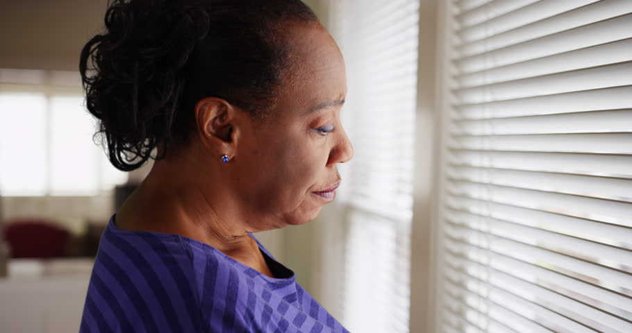 An older black woman mournfully looks out her window. An elderly African American woman sadly looks out her window. 4k Royalty-Free Stock Footage #22769245