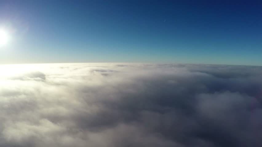 Aerial bird-eye view flying steady altitude above thick clouds towards bright sun beautiful contrast showing crisp blue sky the darker atmosphere above bright sunshine and slowly moving clouds below #22770652