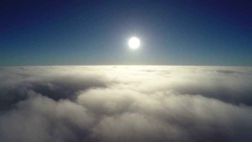 Aerial bird-eye view flying low above thick clouds towards bright sun beautiful contrast showing the crisp blue sky the darker atmosphere above bright sunshine and slowly moving clouds below 4k #22770655