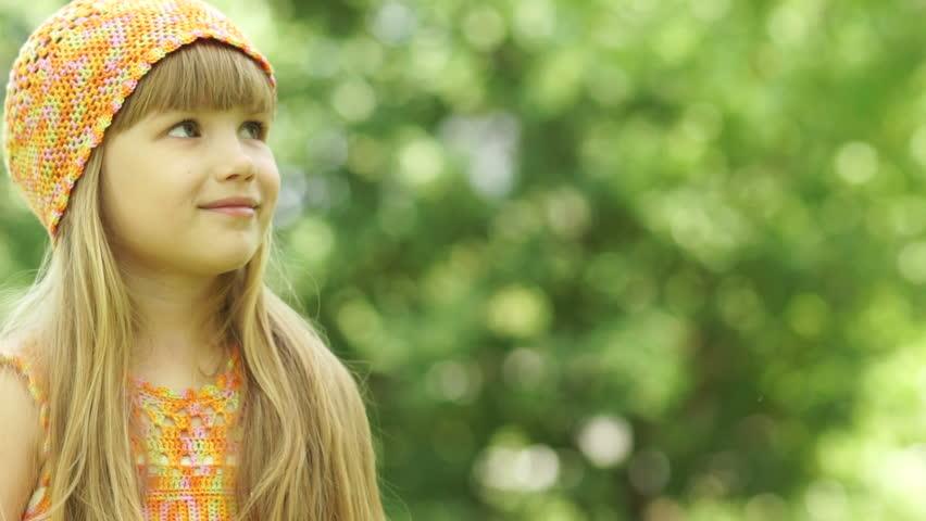 3s girl blowing a dandelion. Close-up portrait.