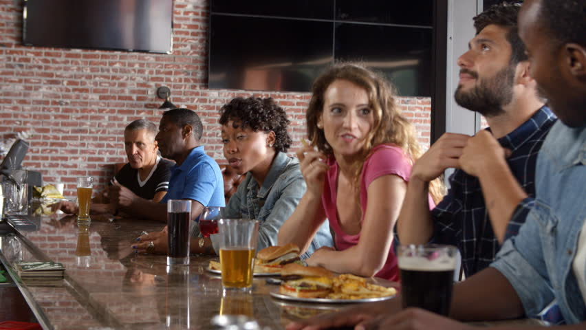 Group Of Friends Watching Game In Sports Bar On Screens #22781782