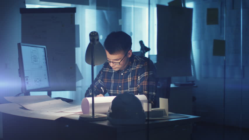 Young Capable Architectural Engineer Working Late Hours in His Office. Office is Dark Only His Table Light is On. Various Plans and Blueprints Lying on the Table. He Writes Down His Calculations.
