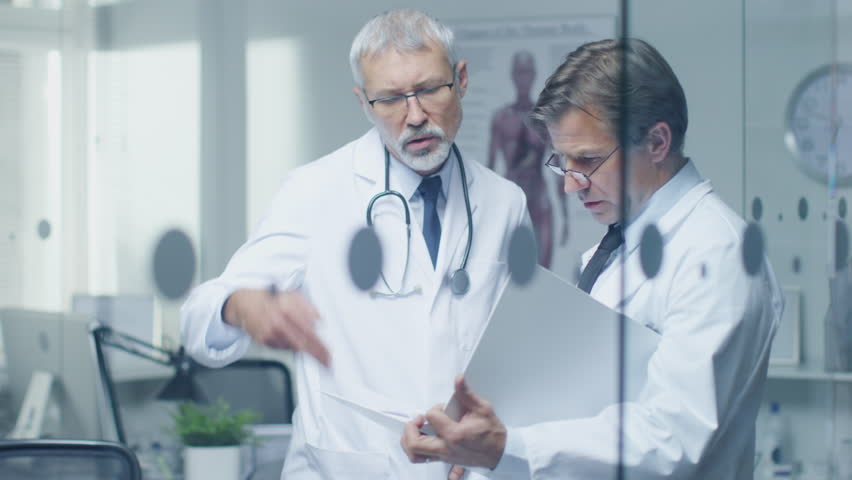 Two Specialist Doctors Discussing Patient's Log. Both are Senior and Experienced. Their Office Looks Modern and Respectable. Shot on RED Cinema Camera in 4K (UHD). | Shutterstock HD Video #22782544