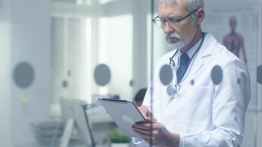 Senior Doctor Thinking About Patient's Diagnosis and Typing on a Tablet Computer. His Office is Bright and Modern. Shot on RED Cinema Camera in 4K (UHD). Royalty-Free Stock Footage #22782553