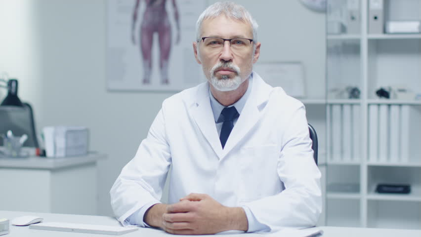 Experienced Gray Haired Senior Medical Practitioner Talking Into Camera. Portrait Shot in Modern and Light Office. Shot on RED Cinema Camera in 4K (UHD). #22782568
