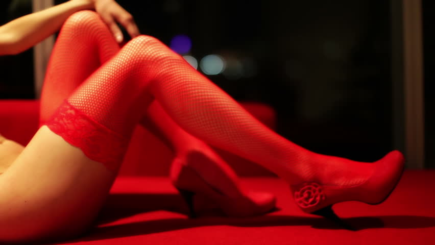 sexy erotic female in a hotel room, close up of her leg in red stockings
