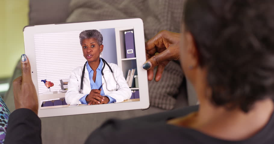 An older black woman talking to her African American doctor via video chat. An elderly black woman talking to her medical professional on her tablet. 4k