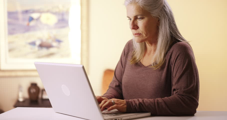 Senior Caucasian woman typing on a laptop computer. Portrait of senior woman using technology to browse media. #22797727
