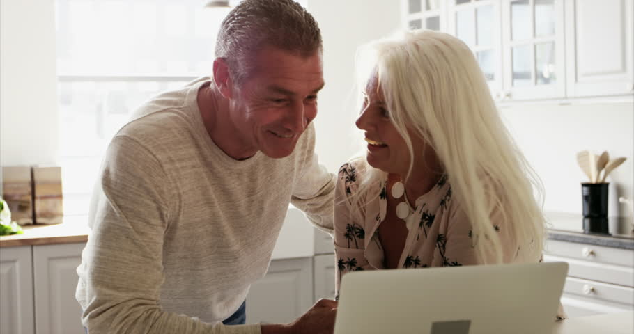 Excited senior couple looking at a laptop together in the kitchen pointing and smiling at something amusing on the screen   Shutterstock HD Video #22818763
