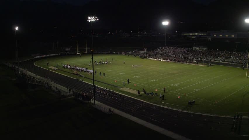 High school football game establishing aerial shot at night under the lights. September 2016