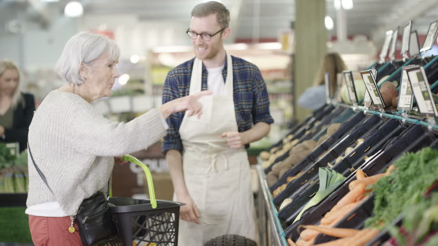 4K Friendly worker in a supermarket assisting senior lady buying groceries Dec 2016-UK | Shutterstock HD Video #22858273