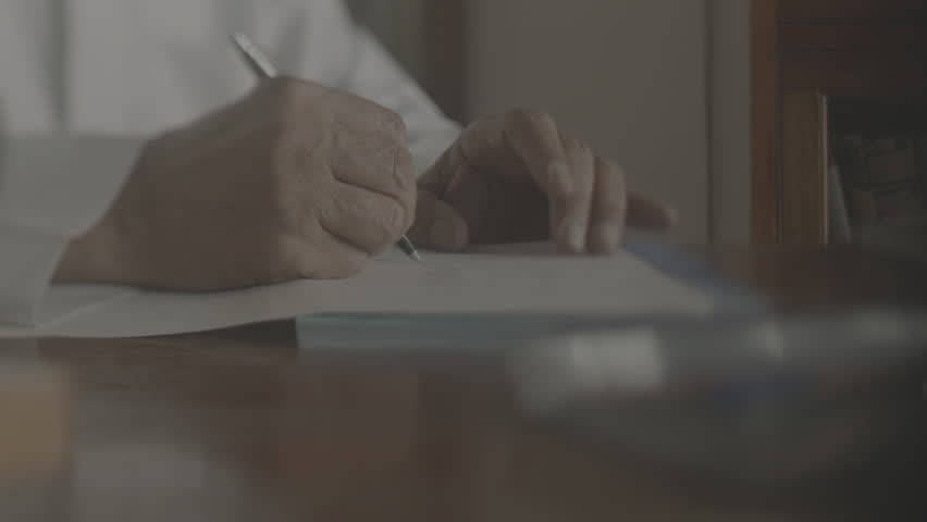 Arab man writing a letter. Tracking shot on the hands of an old Bahraini Arab man writing a letter on a vintage desk.
