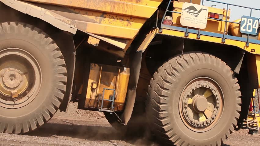Open pit iron ore mining, a big yellow mining truck at work, working in a quarry, big yellow heavy truck in open cast mine, mining of iron ore, the overall plan, Dump Truck, sunny day
