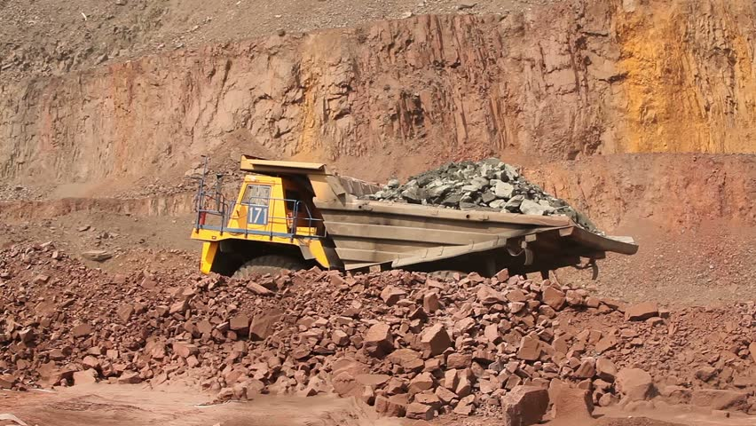 Open pit iron ore mining, a big yellow mining truck at work, working in a quarry, big yellow heavy truck in open cast mine, mining of iron ore, Dump Truck, the overall plan, sunny day