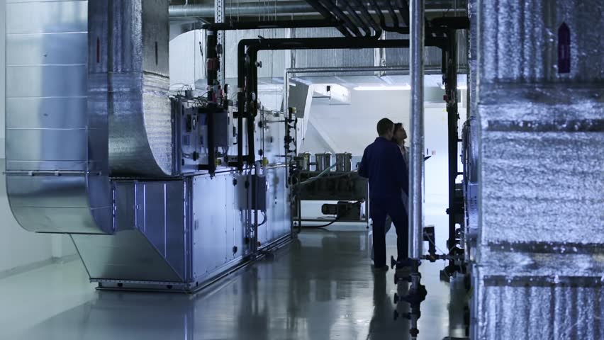 People checks industrial air ducts of a ventilation system on clean and light technical floor
