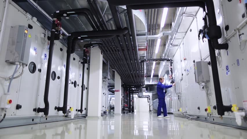 A man checks heating and ventilation systems on the technical floor at an industrial or office building Royalty-Free Stock Footage #22895509