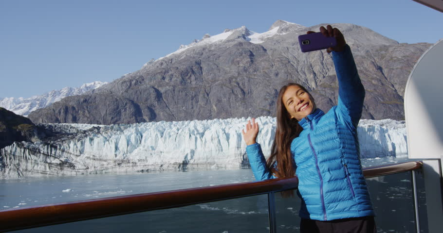 Alaska cruise ship passenger taking selfie photo in Glacier Bay National Park, USA. Woman tourist taking picture using smart phone on travel vacation. Margerie Glacier. RED EPIC SLOW MOTION.
