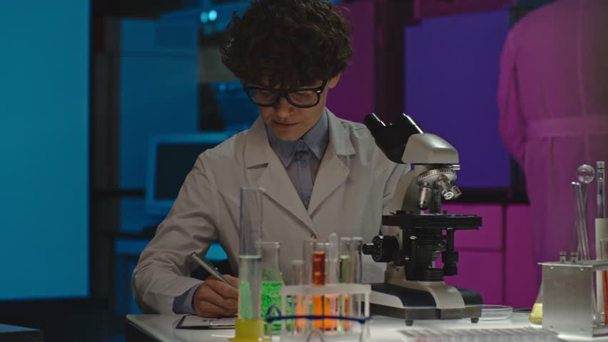 PAN of concentrated curly female scientist in glasses making notes on clipboard and studying sample in microscope, then checking something on tablet   Shutterstock HD Video #22911541
