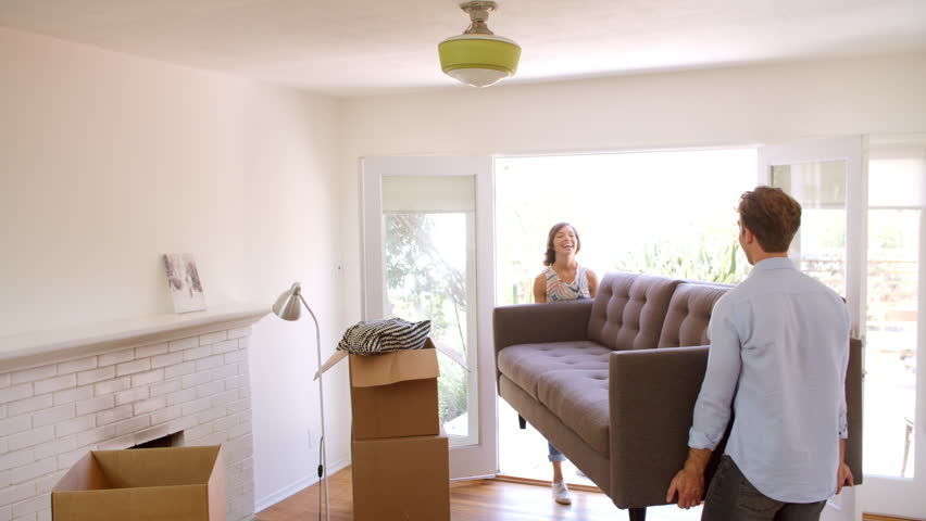 Couple Carrying Sofa Into New Home On Moving Day | Shutterstock HD Video #22923103