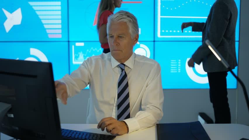 4K Serious mature businessman working on computer in modern office Dec 2016-UK | Shutterstock HD Video #22925032