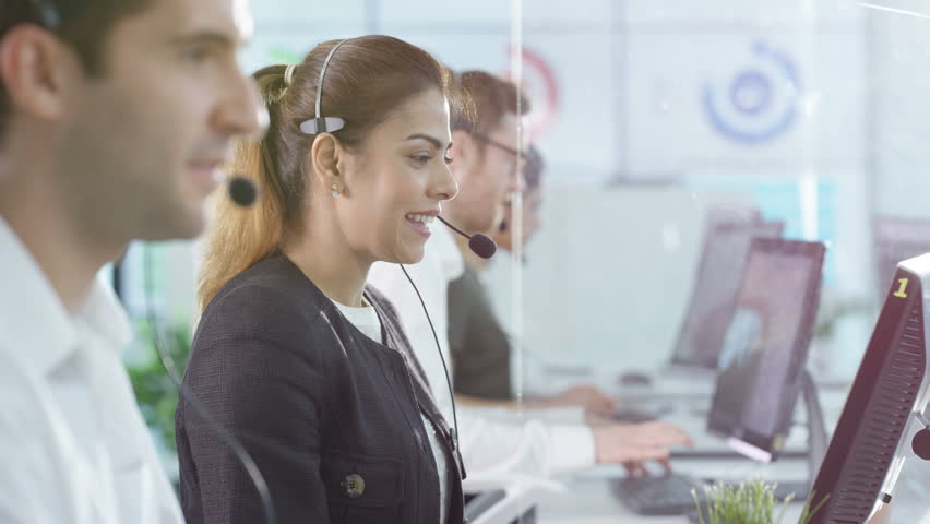4K Portrait smiling customer service operator taking calls in busy call center Dec 2016-UK