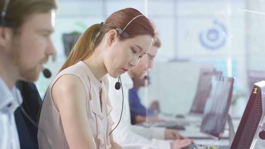 4K Portrait smiling customer service operator taking calls in busy call center Dec 2016-UK | Shutterstock HD Video #22933861