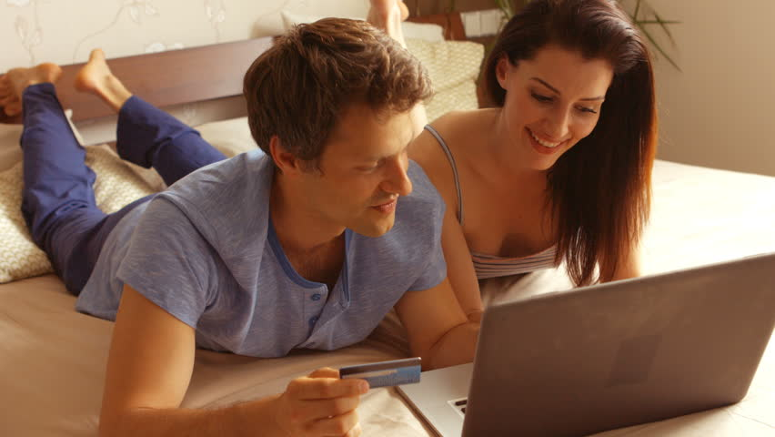 Couple shopping online on laptop using credit card on bed in bedroom 4k #22950262