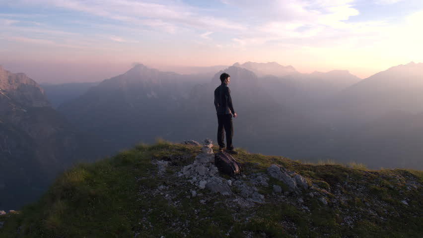 Aerial - Flying from front to behind the man standing on top of the mountain watching beautiful sunset over the peaks | Shutterstock HD Video #22952902