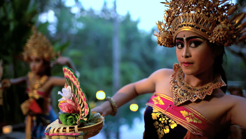 Balinese females performing artistic dance in ceremonial traditional colorful costume using hands and fingers Indonesia South East Asia
