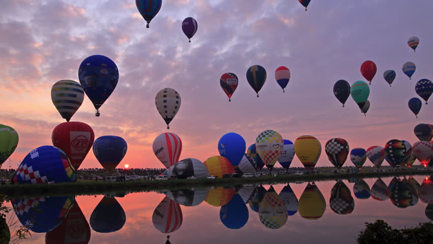 Hot air balloons taking off with beautiful sunrise.