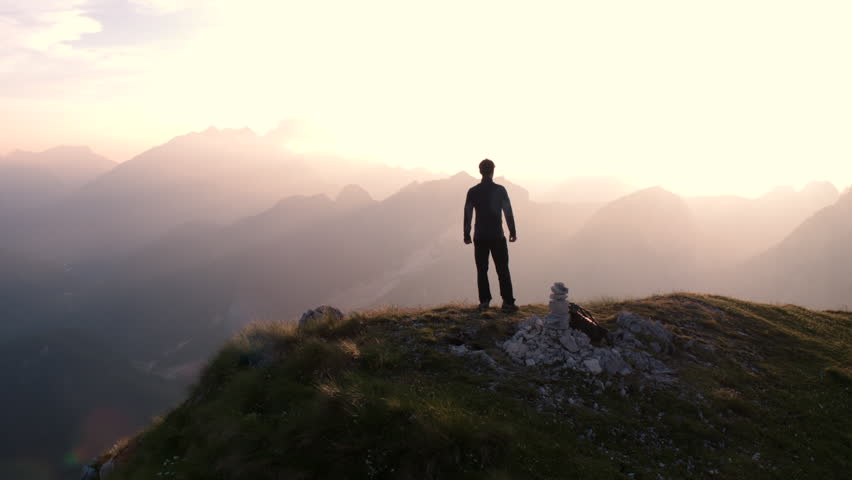 Aerial - Flying around young man standing victoriously on top of the mountain at sunset | Shutterstock HD Video #22960816